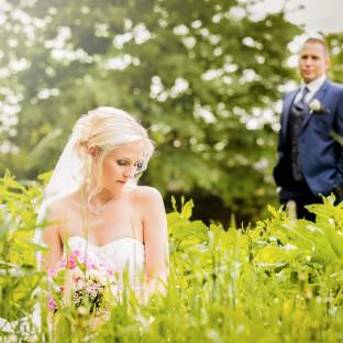 Braut kniet im Feld bei Sonnenschein
