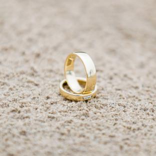 Brautpaar spiegelt sich in Eheringen am Strand