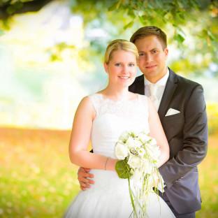 Brautpaar auf Wiese bei Sonnenschein