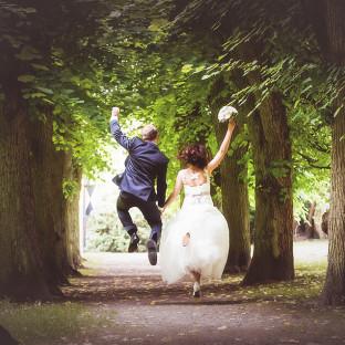 Ehepaar/Brautpaar am Springen mit Brautstrauß. Hochzeitsfoto Reinbek