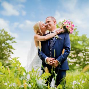 Mann trägt Braut nach Hochzeit mit Brautstrauß