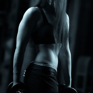 Trainierte Frau mit Hanteln im Fitnesstudio