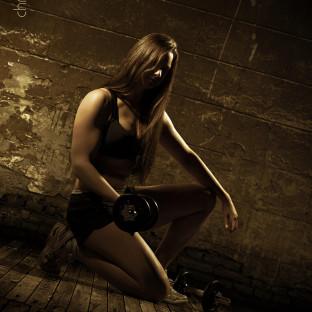 Sportlerin mit Hantel / Fotoshoong von muskulöser Frau