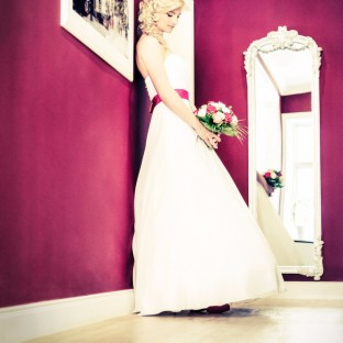 Wunderschöne Braut steht an pinker Wand