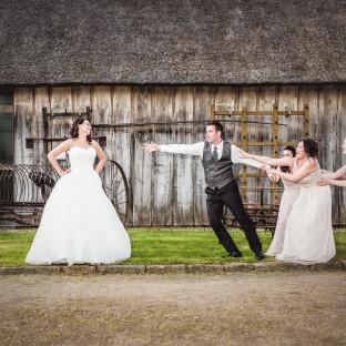 Mann wird von Brautjungfern festgehalten und greift nach seiner Frau